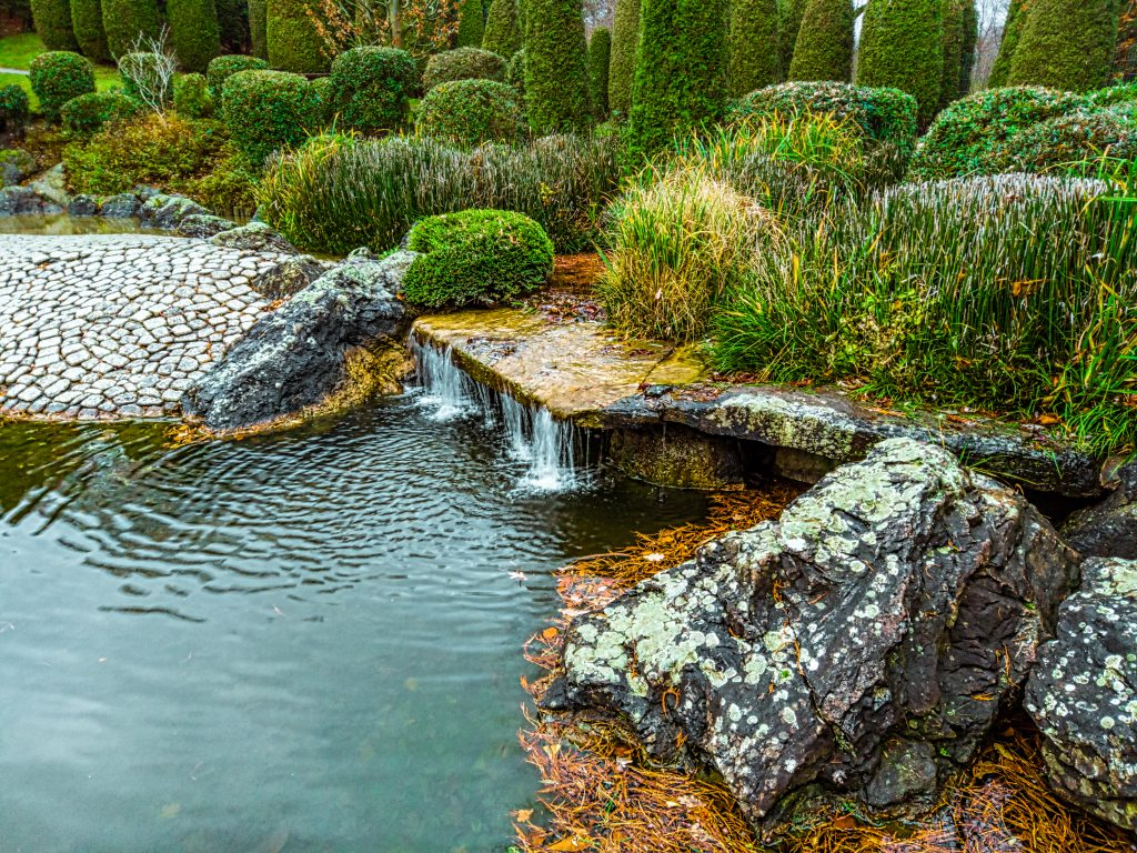On the left side there is a mirror of water, and on the right there is a small waterfall framed by lush vegetation, and in the foreground there are large wild cobbles.